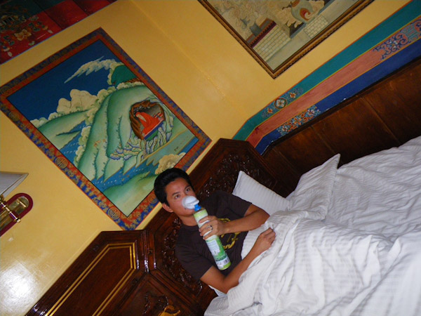 George breathing in a can of oxygen, Lhasa, Tibet